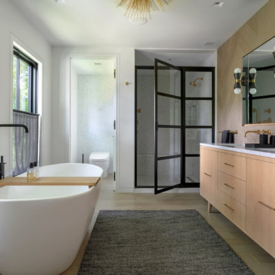 Example of a cottage master beige floor bathroom design in New York with furniture-like cabinets, light wood cabinets, white walls, an undermount sink, a hinged shower door and gray countertops