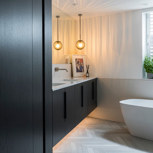 Contemporary bathroom in London with grey floors, flat-panel cabinets, black cabinets, a freestanding bath, beige tiles, white walls, an integrated sink and white worktops.