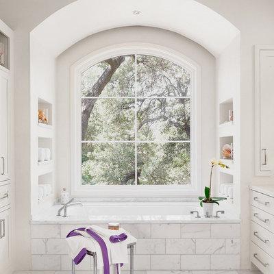 Trendy alcove bathtub photo in Austin with white cabinets and a niche