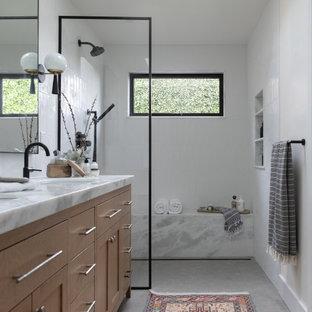 Inredning av ett klassiskt stort vit vitt badrum med dusch, med luckor med infälld panel, skåp i ljust trä, en kantlös dusch, en bidé, vit kakel, porslinskakel, vita väggar, kalkstensgolv, ett undermonterad handfat, marmorbänkskiva, grått golv och dusch med gångjärnsdörr