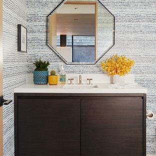 Exemple d'une salle de bain tendance avec un placard à porte plane, des portes de placard en bois sombre, un lavabo encastré et un plan de toilette blanc.