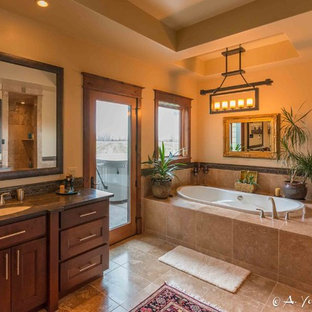 Example of a large mountain style master beige tile, brown tile and ceramic tile travertine floor bathroom design in Other with shaker cabinets, dark wood cabinets, beige walls, an undermount sink and soapstone countertops