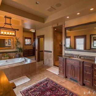Foto de cuarto de baño principal, rústico, grande, con armarios estilo shaker, puertas de armario de madera en tonos medios, bañera encastrada, ducha esquinera, baldosas y/o azulejos beige, baldosas y/o azulejos marrones, baldosas y/o azulejos de cerámica, paredes beige, suelo de travertino, lavabo bajoencimera y encimera de esteatita
