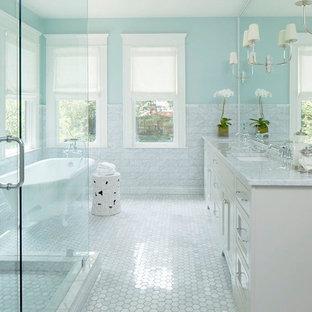Exemple d'une grande douche en alcôve principale chic avec un placard à porte shaker, des portes de placard blanches, une baignoire sur pieds, un WC séparé, un carrelage gris, un carrelage blanc, des carreaux de porcelaine, un mur bleu, un sol en carrelage de terre cuite, un lavabo encastré, un plan de toilette en marbre, un sol blanc et une cabine de douche à porte battante.