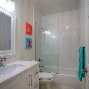 Réalisation d'une petit salle de bain design pour enfant avec un lavabo encastré, un placard à porte shaker, des portes de placard blanches, un plan de toilette en quartz modifié, une baignoire posée, un combiné douche/baignoire, un WC à poser, un carrelage blanc, des carreaux de céramique, un mur gris, un sol en carrelage de porcelaine, un sol beige, une cabine de douche à porte coulissante et un plan de toilette blanc.