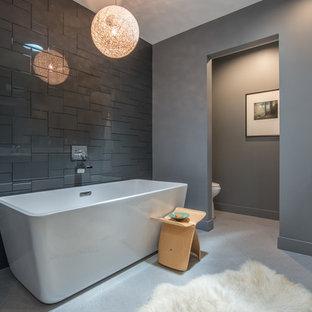 Idee per una stanza da bagno padronale minimal di medie dimensioni con ante lisce, ante nere, vasca freestanding, doccia alcova, WC monopezzo, piastrelle grigie, piastrelle di vetro, pareti grigie, pavimento con piastrelle in ceramica, lavabo sottopiano e top in quarzo composito