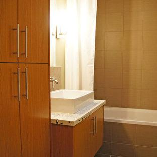 ローリーの中サイズのコンテンポラリースタイルのおしゃれな浴室 (フラットパネル扉のキャビネット、中間色木目調キャビネット、アルコーブ型浴槽、シャワー付き浴槽、分離型トイレ、茶色いタイル、磁器タイル、茶色い壁、磁器タイルの床、オーバーカウンターシンク、テラゾの洗面台、グレーの床、シャワーカーテン) の写真