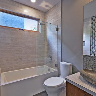Inspiration for a mid-sized contemporary gray tile and porcelain tile porcelain tile bathroom remodel in Portland with a vessel sink, flat-panel cabinets, medium tone wood cabinets, tile countertops, a one-piece toilet and gray walls
