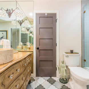 Design ideas for a medium sized mediterranean shower room in Orange County with freestanding cabinets, medium wood cabinets, an alcove bath, a shower/bath combination, a two-piece toilet, multi-coloured tiles, porcelain tiles, beige walls, ceramic flooring, a vessel sink, wooden worktops, multi-coloured floors and brown worktops.