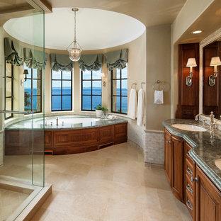 Inspiration pour une grande salle de bain principale traditionnelle avec un placard avec porte à panneau surélevé, des portes de placard en bois brun, une baignoire encastrée, un mur beige, un lavabo encastré, un sol beige, une douche d'angle, un carrelage beige, des carreaux de porcelaine, un sol en travertin, un plan de toilette en granite, une cabine de douche à porte battante et un plan de toilette vert.
