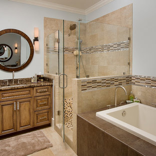 Design ideas for a traditional bathroom in Jacksonville with an undermount sink, raised-panel cabinets, medium wood cabinets, a drop-in tub, an alcove shower, beige tile and brown benchtops.
