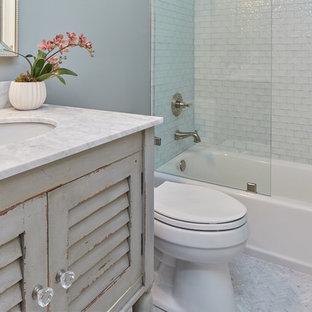 Imagen de cuarto de baño con ducha, tradicional renovado, de tamaño medio, con sanitario de una pieza, baldosas y/o azulejos azules, baldosas y/o azulejos de vidrio, suelo de baldosas de porcelana, lavabo bajoencimera, suelo blanco, ducha abierta, armarios con puertas mallorquinas, puertas de armario con efecto envejecido, bañera empotrada, combinación de ducha y bañera, encimera de cuarzo compacto y paredes grises