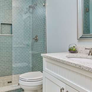 Mid-sized beach style 3/4 bathroom in Other with shaker cabinets, white cabinets, an open shower, a one-piece toilet, blue tile, glass tile, blue walls, porcelain floors, an undermount sink, recycled glass benchtops, white floor and an open shower.