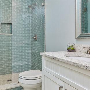 Cette photo montre une salle d'eau bord de mer de taille moyenne avec un placard à porte shaker, des portes de placard blanches, une douche ouverte, un WC à poser, un carrelage bleu, un carrelage en pâte de verre, un mur bleu, un sol en carrelage de porcelaine, un lavabo encastré, un plan de toilette en verre recyclé, un sol blanc et aucune cabine.