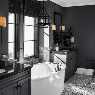 Idéer för att renovera ett vintage svart svart badrum med dusch, med luckor med upphöjd panel, svarta skåp, ett fristående badkar, grå kakel, svarta väggar, ett undermonterad handfat och grått golv