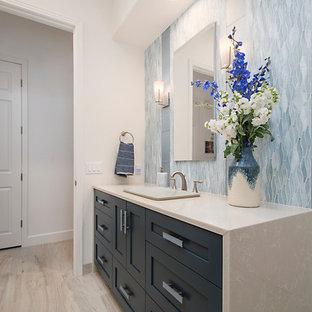 Idee per una stanza da bagno con doccia tradizionale di medie dimensioni con ante in stile shaker, ante blu, doccia alcova, WC monopezzo, piastrelle blu, piastrelle di vetro, pareti bianche, pavimento in gres porcellanato, lavabo da incasso, top in quarzo composito, porta doccia a battente e top bianco