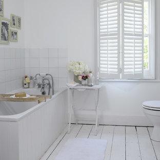 ドーセットのカントリー風おしゃれな浴室 (コーナー型浴槽、白いタイル、白い壁、塗装フローリング、白い床) の写真