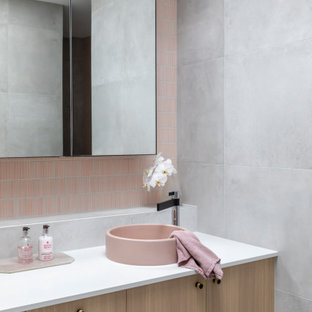 Photo of a contemporary bathroom in Sydney with flat-panel cabinets, light wood cabinets, pink tile, mosaic tile, a vessel sink, white benchtops, a double vanity and a floating vanity.