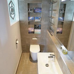 サセックスの小さいコンテンポラリースタイルのおしゃれなバスルーム (浴槽なし) (フラットパネル扉のキャビネット、白いキャビネット、バリアフリー、一体型トイレ、茶色いタイル、セラミックタイル、白い壁、セラミックタイルの床、一体型シンク、茶色い床、開き戸のシャワー、ニッチ、洗面台1つ、折り上げ天井、フローティング洗面台) の写真