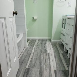 Imagen de cuarto de baño con ducha, contemporáneo, de tamaño medio, con armarios con paneles lisos, puertas de armario blancas, bañera encastrada, ducha empotrada, sanitario de una pieza, baldosas y/o azulejos blancos, baldosas y/o azulejos de cerámica, paredes verdes, lavabo integrado, encimera de vidrio, suelo gris, ducha con cortina y encimeras verdes