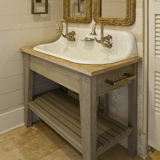 Ejemplo de cuarto de baño con ducha, tropical, de tamaño medio, con armarios abiertos, sanitario de dos piezas, paredes beige, suelo de travertino, lavabo de seno grande, encimera de madera, puertas de armario de madera clara y encimeras beige