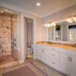 Foto di una grande stanza da bagno padronale chic con ante con riquadro incassato, ante bianche, doccia alcova, WC monopezzo, pareti grigie, pavimento in marmo, lavabo sottopiano, top in vetro, pavimento beige e porta doccia a battente