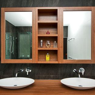Imagen de cuarto de baño principal, minimalista, grande, con lavabo sobreencimera, armarios tipo vitrina, puertas de armario de madera oscura, encimera de madera, baldosas y/o azulejos grises y paredes multicolor