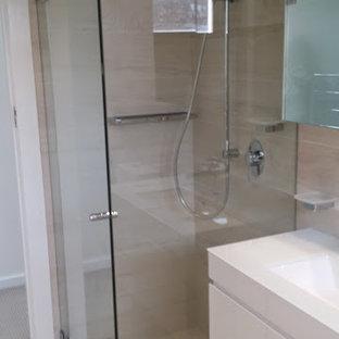 Modelo de cuarto de baño principal, moderno, pequeño, con lavabo bajoencimera, armarios con paneles lisos, puertas de armario blancas, encimera de vidrio, bañera exenta, ducha esquinera, sanitario de pared, baldosas y/o azulejos beige, baldosas y/o azulejos de porcelana, paredes beige y suelo de baldosas de porcelana