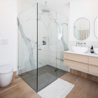 Cette image montre une grand salle d'eau design avec des portes de placard en bois clair, une douche d'angle, un WC à poser, un carrelage blanc, du carrelage en marbre, un mur blanc, une vasque, un plan de toilette en quartz modifié, une cabine de douche à porte battante, un plan de toilette blanc, meuble double vasque, meuble-lavabo suspendu, un plafond voûté, du lambris, un placard à porte plane, un sol marron et une niche.
