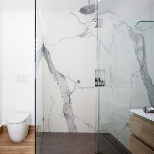 Неиссякаемый источник вдохновения для домашнего уюта: главная ванная комната в стиле модернизм с светлыми деревянными фасадами, угловым душем, унитазом-моноблоком, белой плиткой, мраморной плиткой, белыми стенами, светлым паркетным полом, настольной раковиной, столешницей из искусственного кварца, душем с распашными дверями, белой столешницей, тумбой под две раковины, подвесной тумбой, сводчатым потолком и панелями на части стены