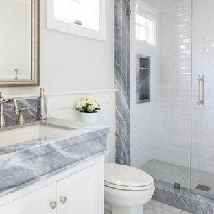 На фото: ванная комната в морском стиле с фасадами с декоративным кантом, белыми фасадами, душем в нише, белыми стенами, врезной раковиной, белым полом, душем с распашными дверями, серой столешницей, нишей, тумбой под одну раковину, встроенной тумбой и панелями на стенах с