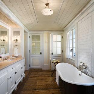 Maritimes Badezimmer mit Unterbauwaschbecken, Schrankfronten mit vertiefter Füllung, weißen Schränken, freistehender Badewanne, weißen Fliesen, Metrofliesen, gelber Wandfarbe und dunklem Holzboden in New York