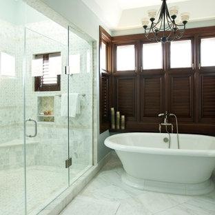 Modelo de cuarto de baño principal, exótico, extra grande, con puertas de armario de madera en tonos medios, bañera exenta, combinación de ducha y bañera, baldosas y/o azulejos blancos, baldosas y/o azulejos en mosaico, paredes grises, suelo de mármol y encimera de mármol