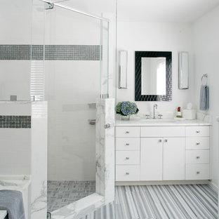 Esempio di una grande stanza da bagno padronale tradizionale con ante lisce, ante bianche, vasca sottopiano, doccia ad angolo, piastrelle grigie, piastrelle bianche, piastrelle di vetro, pareti bianche, pavimento in laminato, lavabo sottopiano, top in marmo, pavimento grigio e porta doccia a battente
