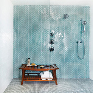 This is an example of a beach style master bathroom in New York with an alcove shower, blue tile, mosaic tile floors, grey floor, a hinged shower door and glass tile.