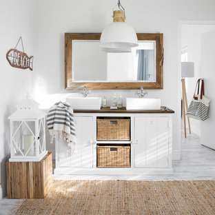 This is an example of a coastal bathroom in London with white cabinets, white walls, a vessel sink and white floors.