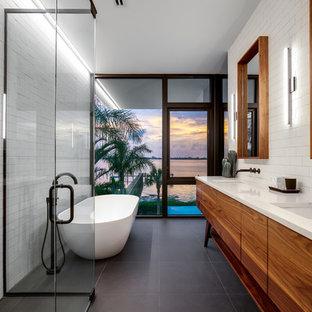 Bild på ett mellanstort funkis vit vitt en-suite badrum, med möbel-liknande, skåp i mellenmörkt trä, ett fristående badkar, en kantlös dusch, vit kakel, tunnelbanekakel, klinkergolv i porslin, ett undermonterad handfat, bänkskiva i kvarts, dusch med gångjärnsdörr, grått golv och vita väggar