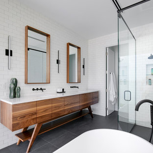 Inspiration for a mid-sized contemporary master white tile and subway tile porcelain floor and gray floor bathroom remodel in Tampa with furniture-like cabinets, medium tone wood cabinets, a two-piece toilet, white walls, an undermount sink, quartz countertops, a hinged shower door and white countertops