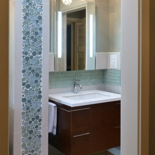Imagen de cuarto de baño principal, clásico renovado, pequeño, con armarios con paneles lisos, puertas de armario de madera en tonos medios, bañera empotrada, ducha empotrada, sanitario de una pieza, baldosas y/o azulejos azules, baldosas y/o azulejos de vidrio, paredes grises, suelo de bambú, lavabo suspendido y encimera de cuarcita