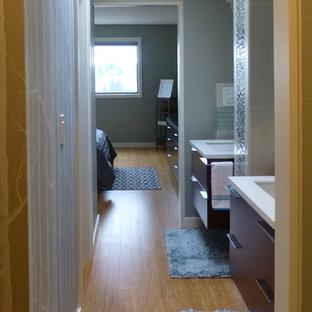 Modelo de cuarto de baño principal, tradicional renovado, pequeño, con armarios con paneles lisos, puertas de armario de madera en tonos medios, bañera empotrada, ducha empotrada, sanitario de una pieza, baldosas y/o azulejos azules, baldosas y/o azulejos de vidrio, paredes grises, suelo de bambú, lavabo suspendido y encimera de cuarcita