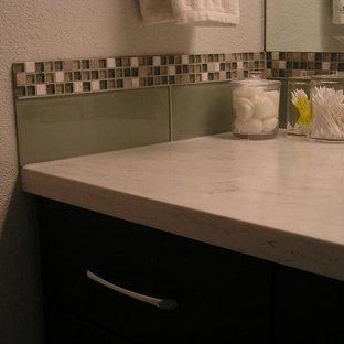 Diseño de cuarto de baño principal, de estilo zen, de tamaño medio, con armarios con paneles lisos, puertas de armario negras, ducha doble, sanitario de dos piezas, baldosas y/o azulejos multicolor, baldosas y/o azulejos de vidrio laminado, paredes grises, suelo de baldosas de cerámica, lavabo bajoencimera, encimera de acrílico y suelo gris