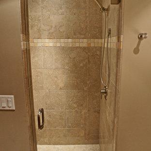 Пример оригинального дизайна: детская ванная комната среднего размера в классическом стиле с врезной раковиной, ванной на ножках, душем в нише, коричневой плиткой, каменной плиткой, бежевыми стенами, полом из известняка, фасадами с утопленной филенкой, бежевыми фасадами, столешницей из известняка и унитазом-моноблоком