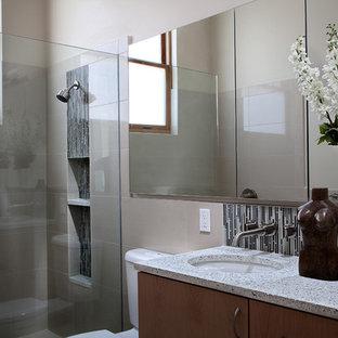 Ispirazione per una stanza da bagno padronale design di medie dimensioni con lavabo sottopiano, ante lisce, ante in legno chiaro, top in vetro riciclato, doccia aperta, WC a due pezzi, piastrelle beige, piastrelle in ceramica, pareti beige e pavimento con piastrelle in ceramica