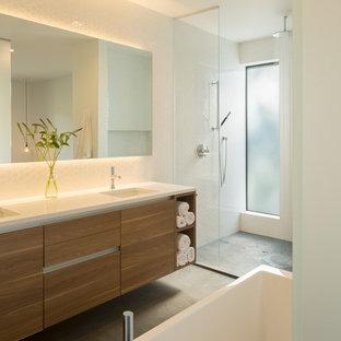 オレンジカウンティの大きいコンテンポラリースタイルのおしゃれなマスターバスルーム (フラットパネル扉のキャビネット、中間色木目調キャビネット、置き型浴槽、オープン型シャワー、白いタイル、セラミックタイル、白い壁、コンクリートの床、アンダーカウンター洗面器、珪岩の洗面台) の写真