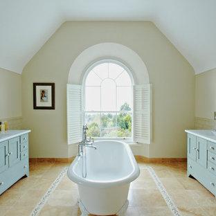 Ejemplo de cuarto de baño tradicional con bañera exenta, baldosas y/o azulejos de cemento y puertas de armario verdes