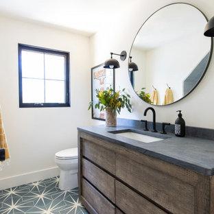 Esempio di una stanza da bagno country con ante lisce, ante in legno bruno, pareti bianche, lavabo sottopiano, pavimento blu e top grigio