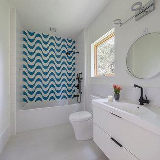 Diseño de cuarto de baño con ducha, minimalista, de tamaño medio, con armarios con paneles lisos, puertas de armario de madera oscura, bañera empotrada, combinación de ducha y bañera, sanitario de una pieza, baldosas y/o azulejos azules, baldosas y/o azulejos de cemento, paredes amarillas, suelo de baldosas de porcelana, lavabo integrado, encimera de terrazo y ducha con cortina