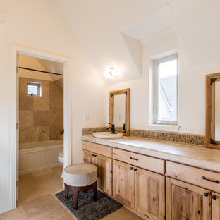 Example of a mid-sized mountain style master beige tile and stone tile bathroom design in Denver with beige cabinets, a one-piece toilet, beige walls, a drop-in sink and granite countertops