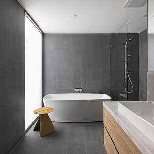 Design ideas for a modern master bathroom in Melbourne with flat-panel cabinets, beige cabinets, a freestanding tub, a corner shower, gray tile, grey walls, a vessel sink, grey floor, an open shower and white benchtops.