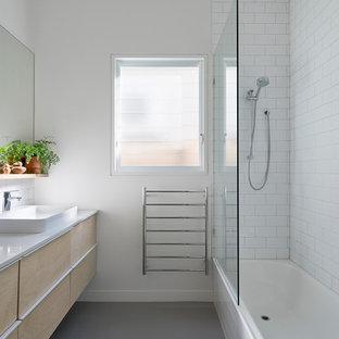 На фото: с невысоким бюджетом маленькие ванные комнаты в скандинавском стиле с светлыми деревянными фасадами, душем над ванной, раздельным унитазом, белой плиткой, плиткой кабанчик, белыми стенами, полом из линолеума, столешницей из кварцита, накладной раковиной и ванной в нише